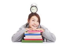 Szczęśliwy młody studencki przyglądający zegar z książkami Obraz Royalty Free