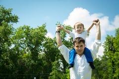 Szczęśliwy młody syn na jego brać na swoje barki ojca Zdjęcia Stock