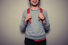 Szczęśliwy młody uczeń z czerwonym plecakiem fotografia stock