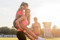 Szczęśliwy młody wiman piggybacking jej przyjaciela przy stadium obraz royalty free