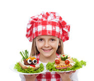 Szczęśliwy mała dziewczynka szef kuchni z kreatywnie kanapkami zdjęcia stock