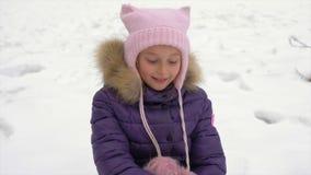 Szczęśliwy mała dziewczynka uśmiech, sztuka z oczami i Młoda caucasian dziewczyna siedzi przy śniegiem przy zimą Dziewczyny use ś zbiory