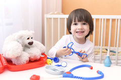 Szczęśliwy małe dziecko bawić się lekarkę obraz stock