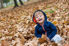 Szczęśliwy małe dziecko, chłopiec śmia się i bawić się w jesieni Obrazy Royalty Free
