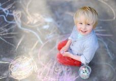 Szczęśliwy małe dziecko chłopiec obsiadanie i rysunek z barwioną kredą na asfalcie obraz royalty free