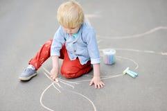 Szczęśliwy małe dziecko chłopiec rysunek z barwioną kredą na asfalcie zdjęcia stock
