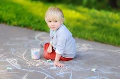 Szczęśliwy małe dziecko chłopiec rysunek z barwioną kredą na asfalcie obraz royalty free