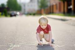 Szczęśliwy małe dziecko chłopiec rysunek z barwioną kredą na asfalcie zdjęcie stock