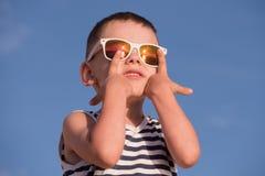 Szczęśliwy małe dziecko jest ubranym okulary przeciwsłonecznych i pasiastą koszula na niebieskiego nieba tle Zdjęcie Royalty Free