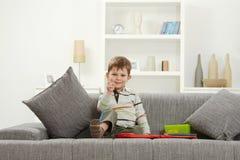 Szczęśliwy małe dziecko siedzi na kanapie z zabawkami zdjęcia royalty free
