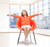 Szczęśliwy małej dziewczynki obsiadanie na projektanta krześle Fotografia Stock