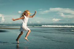 Szczęśliwy małej dziewczynki odprowadzenie przy plażą Zdjęcie Stock