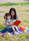 Szczęśliwy mały śliczny dziewczynka uśmiech i czytająca książka z matką, mama mówimy opowieść jego córka w lato parka szczęśliwej zdjęcie royalty free