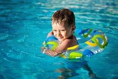 Szczęśliwy Mały caucasian chłopiec uczenie pływanie z ciułaczem w basenie, zębu smiley życie pierścionek cieszy się w dopłynięciu zdjęcie royalty free