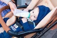 Szczęśliwy mały dziecka obsiadanie w spacerowiczu i pić od butelki mleko, w zimie odziewamy pojęcia jedzenia pierś Obraz Stock