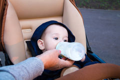 Szczęśliwy mały dziecka obsiadanie w spacerowiczu i pić od butelki mleko, w zimie odziewamy pojęcia jedzenia pierś Obrazy Stock