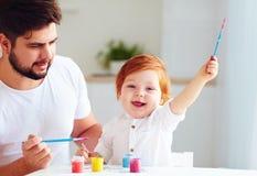 Szczęśliwy mały dziecko artysty rysunek z kolorowymi farbami i ojcem w domu Zdjęcie Royalty Free