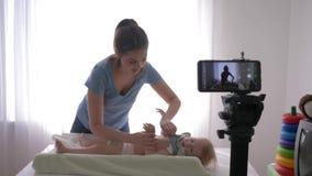 Szczęśliwy macierzyństwo, popularni vlogger kobiety zmian ubrania chłopiec podczas gdy nagrywający nauczania wideo na telefonie k zbiory