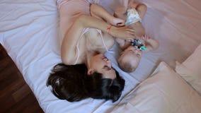 Szczęśliwy macierzysty bawić się w łóżku z nowonarodzonym dzieckiem zbiory wideo