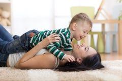 Szczęśliwy macierzysty bawić się z dzieciakiem na podłoga w dziecko pokoju Zdjęcia Royalty Free
