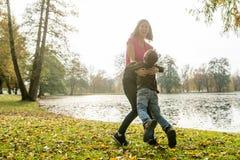 Szczęśliwy macierzysty bawić się z jej dzieciakiem w jesieni Zdjęcia Stock