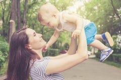 Szczęśliwy macierzysty bawić się z jej dzieckiem w parku fotografia royalty free