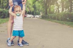 Szczęśliwy macierzysty bawić się z jej dzieckiem w parku zdjęcia royalty free