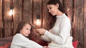 Szczęśliwy macierzysty czesanie jej córki ` s włosy podczas gdy śpiewa Bożenarodzeniową piosenkę Obrazy Stock
