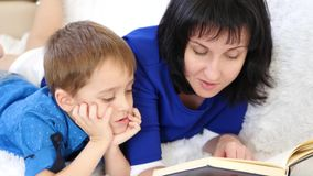 Szczęśliwy macierzysty czytanie książka jej dziecko na białej kanapie