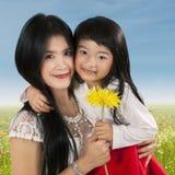 Szczęśliwy macierzysty mienie kwiat z jej dzieckiem Fotografia Stock