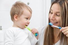 Szczęśliwy macierzysty nauczanie jej syn dlaczego krzaków zęby Zdjęcia Stock
