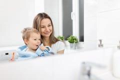 Szczęśliwy macierzysty nauczanie jej syn dlaczego krzaków zęby Obraz Stock