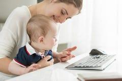 Szczęśliwy macierzysty obsiadanie przy komputerem i mieniem jej dziecko na podołku Obrazy Stock