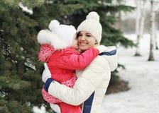 Szczęśliwy macierzysty przytulenia dziecko blisko choinki w zima dniu zdjęcie stock