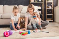 Szczęśliwy macierzysty rysunek z jej dziećmi zdjęcia royalty free