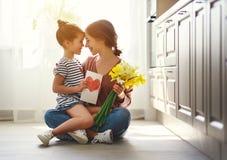 Szczęśliwy matka dzień! dziecko córka daje matce bukietowi kwiaty narcyz i prezent zdjęcia royalty free