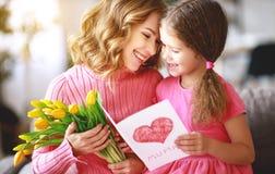 Szczęśliwy matka dzień! dziecko córka daje matce bukietowi kwiaty tulipany i pocztówka obraz stock