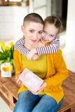 Szczęśliwy matka urodziny lub dnia tło Urocza młoda dziewczyna zaskakuje mamy, młodego pacjenta z nowotworem z bukietem i teraźni zdjęcie stock