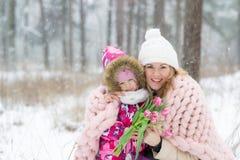 Szczęśliwy matki i córki odprowadzenie w Śnieżnym lesie, Pastelowych menchii Merynosowej wełny Gigantyczna koc, zimna pogoda obrazy royalty free