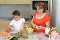Szczęśliwy matki i syna narządzanie je lunch w kuchni zdjęcie royalty free