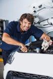 Szczęśliwy mechanik Egzamininuje Samochodowego silnika Zdjęcie Royalty Free