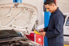 Szczęśliwy mechanik sprawdza baterię fotografia royalty free