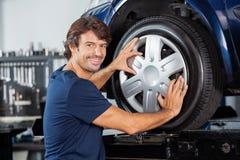 Szczęśliwy mechanika naprawiania aliaż Samochodowa opona fotografia royalty free