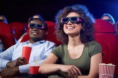 Szczęśliwy międzynarodowy pary łasowania popkorn w kinie fotografia stock