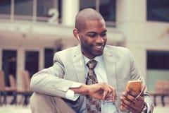 Szczęśliwy miastowy fachowy mężczyzna używa mądrze telefon słucha muzyka Obraz Stock