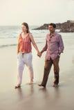Szczęśliwy mieszany biegowy pary odprowadzenie na plaży zdjęcie royalty free