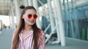 Szczęśliwy moda model w czerwonych okularach przeciwsłonecznych chodzi ufnego wzdłuż ulicznego pobliskiego centrum handlowego mło zbiory