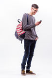 Szczęśliwy modnisia facet w szkłach z plecakiem używać mądrze telefon słuchać muzykę z hełmofonami obraz royalty free