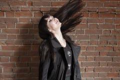 Szczęśliwy modnisia gila potrząśnięcie jej hairs przeciw czerwonemu ściana z cegieł z copyspace Zdjęcie Royalty Free