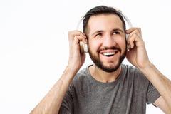 Szczęśliwy modnisia mężczyzna, ono uśmiecha się podczas gdy słuchający muzyka na hełmofonach Na białym tle fotografia royalty free